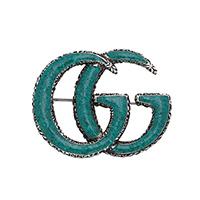 Эмалированная брошь зеленого цвета Gucci GG Marmont в виде эмблемы бренда, фото